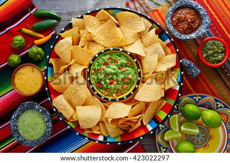Nachos with guacamole tortilla chips in sombrero plate and sauces - stock photo