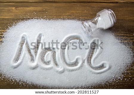 NaCl written on a heap of salt - Sodium Chloride - stock photo