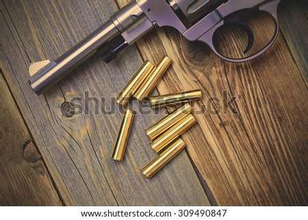 Nagan revolver with cartridges on aged wood background, close-up, part of. instagram image filter retro style - stock photo