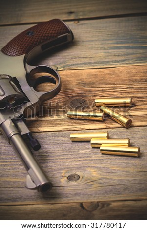 Nagan revolver with cartridges on aged wood boards, close-up. instagram image filter retro style - stock photo