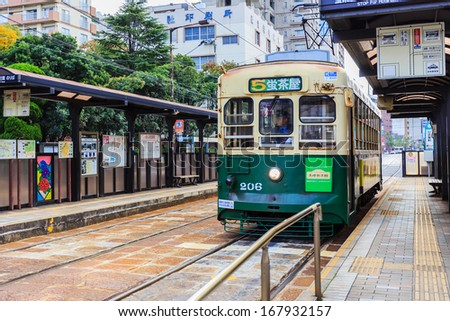 NAGASAKI, JAPAN - NOVEMBER 14: Tram in Nagasaki, Japan on November 14, 2013. Served by 4 tram lines, operated by Nagasaki Electric Tramway, provide easy access to most city's main attractions - stock photo