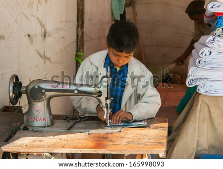 NAGAUR, INDIA - CIRCA FEBRUARY 2011: Child labor, boy sewing in booth on the market. - stock photo