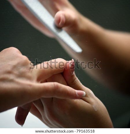 Nail beautician polishing nails - stock photo