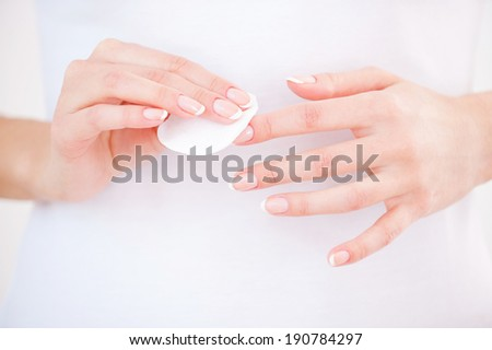 Nail care. Close-up of woman cleaning nails with cotton pad - stock photo