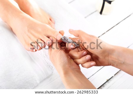 Nail clipping, cutting skins pedicure treatment.Foot care treatment and nail, the woman at the beautician for pedicure. - stock photo