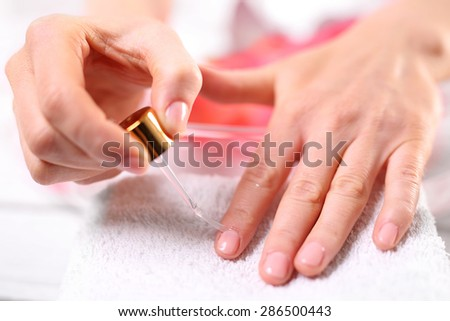 Nail painting. Woman paints the nails cuticle oil and nail - stock photo