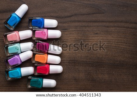 nail polish bottles of different colors on brown wooden table - stock photo