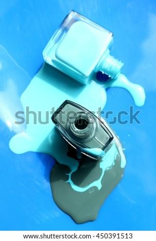 Nail polish enamel liquid two bottles on blue background - stock photo