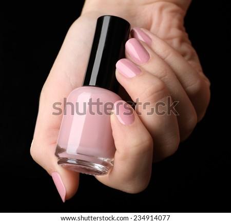 Nail polish in hand, close-up - stock photo