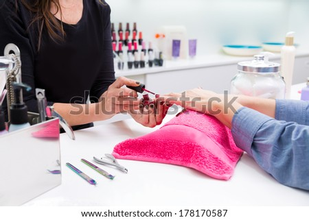 Nail saloon woman painting color nail polish in hands over pillow with pink towel - stock photo