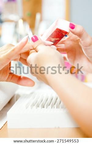 Nail treatment in beauty salon - stock photo