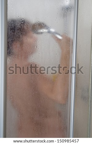 naked and invisible woman middle age in a shower with a shower head in Hand  - stock photo