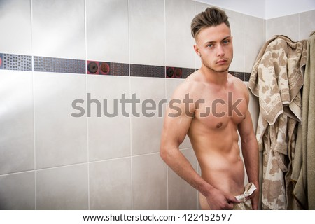 Naked Athletic Young Man Ready for Having a Bath at the Bathroom to Refresh - stock photo