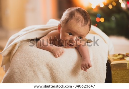 Naked baby boy lying on stomach in basket next to fireplace - stock photo