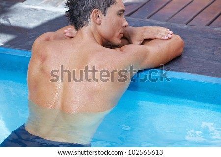Naked back of attractive man in a swimming pool - stock photo