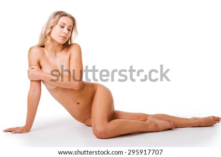 Naked beauty. Beautiful young naked woman covering breasts with hand and keeping eyes closed while sitting on the floor and in front of the white background - stock photo