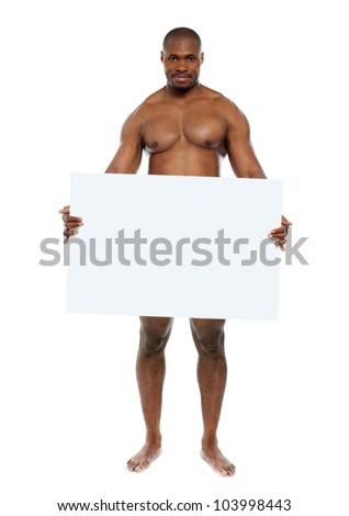 Naked black man hiding behind blank white billboard. Copy space - stock photo