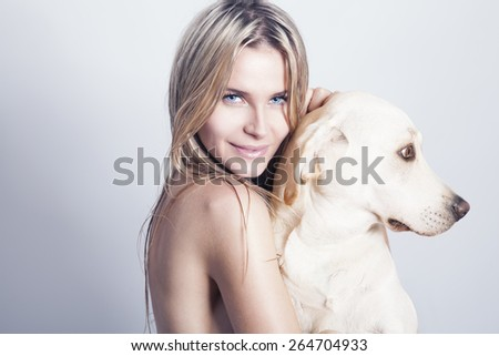 Naked blonde woman with her dog, studio shot. horizontal - stock photo