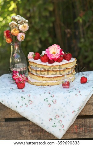 Naked cake with strawberries and flowers - stock photo
