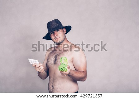 Naked corpulent man in hat holding pharmaceutical products and lettuce. - stock photo