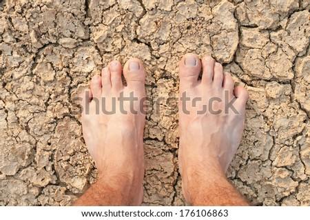 Naked Feet on dry Soil - stock photo