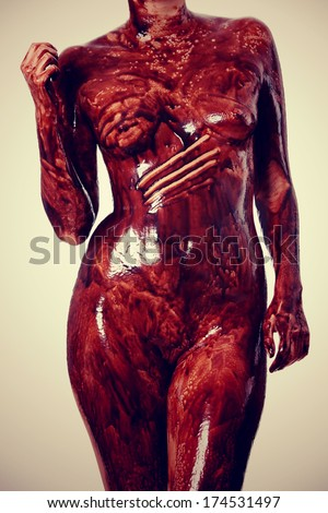 Naked female body covered with chocolate - stock photo