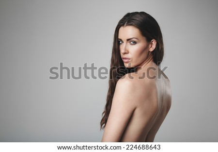 Naked female model posing on grey background. Topless caucasian woman looking at you. - stock photo
