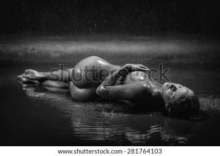 naked girl on a beach in the rain - stock photo