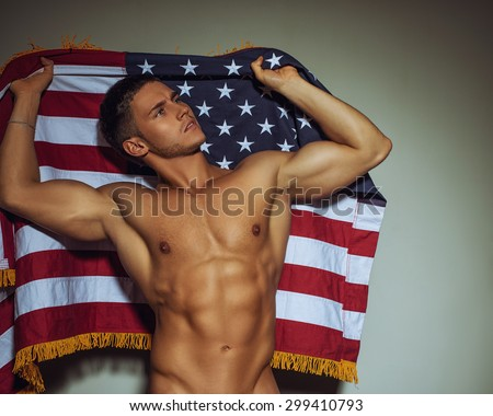 Naked handsome fitness guy standing against the wall with American flag - stock photo
