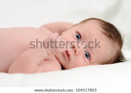 Naked Infant Lying on Back. One month old baby boy lying on his back while naked. Shallow DOF. - stock photo