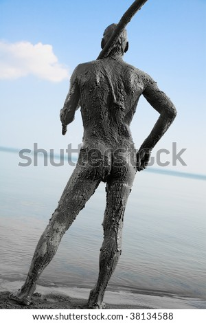 naked man covered in mud with a spear - stock photo