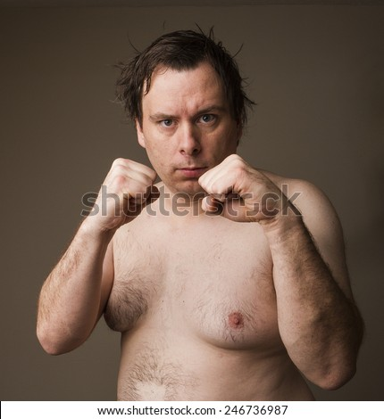 Naked man holding up his hands trying to fight - stock photo