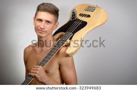 naked man with bass guitar - stock photo