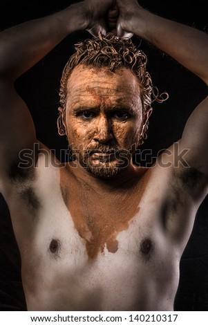 naked man with his face covered in clay - stock photo