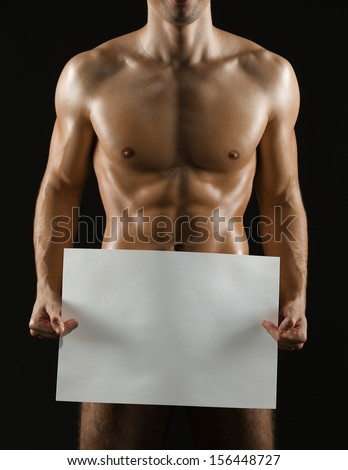 Naked sportive man hands large white sheet of paper copyspace, isolated on black - stock photo