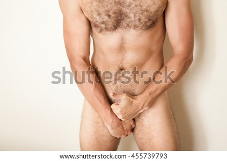 Naked sporty Caucasian man cover his genitals with hands and shows thumb up gesture, male body beauty, close up studio photo - stock photo
