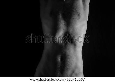 Naked torso of young man on black background - stock photo
