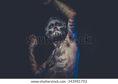 naked wild man with tribal paint - stock photo