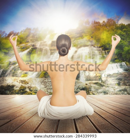Naked woman doing yoga sitting on jetty - stock photo