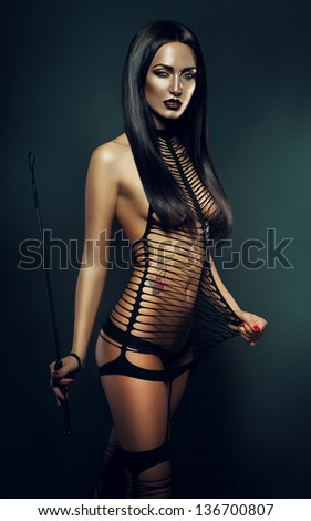 naked woman in costume with whip - stock photo