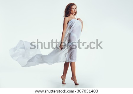 Naked woman in transparent cloth looking away  at copyspace while standing over white background. Sensual young woman posing in studio with a white scarf on her body. - stock photo