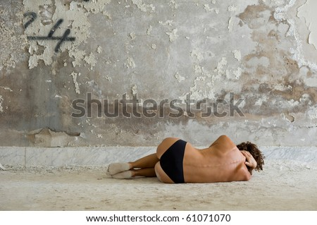 Naked woman laying on the floor in a abandoned room. - stock photo
