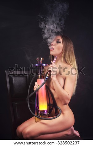 Naked woman smoking hookah - stock photo