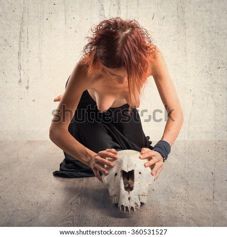 Naked woman with horse skull - stock photo