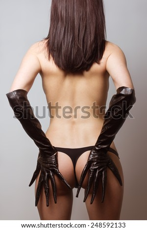 naked young girl in leather latex gloves, catwoman style  - stock photo