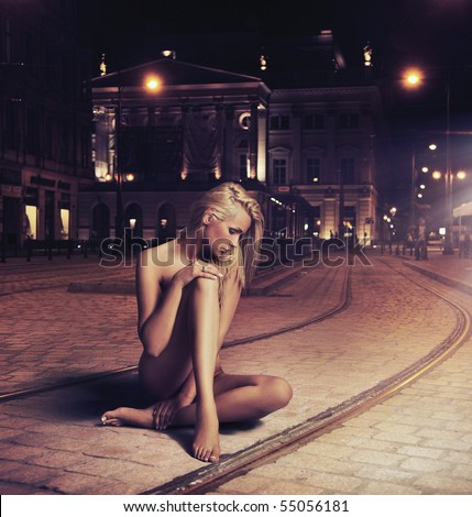 Naked young woman in sensual pose on the street - stock photo