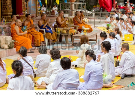 NAKHON PATHOM, THAILAND, JANUARY 16, 2016 : Buddhist monks and women are chanting and praying outside the Wat Samphran temple in Nakhon Pathom near Bangkok, Thailand  - stock photo