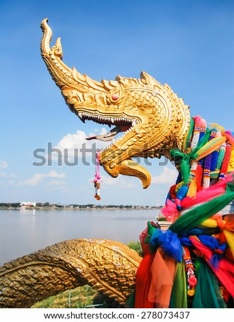 NAKHON PHANOM , THAILAND : The golden serpent head of naga statue on blue sky background is located on the banks of Mekong River in Thailand. - stock photo