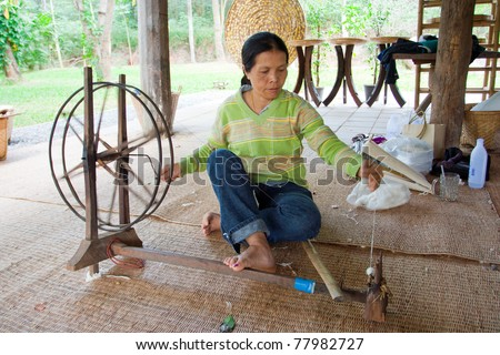 NAKHON-RATCHASIMA, THAILAND - DECEMBER 25: Traditional old style for pulling out silk thread from the cocoon and spining them to keep on spool on December 25, 2008 in Nakhon-Ratchasima, Thailand. - stock photo