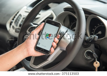 NAKORN PATHOM, THAILAND - FEB 11, 2016: A man hand holding screen shot of Google map app showing on iPhone 6 in the car. - stock photo